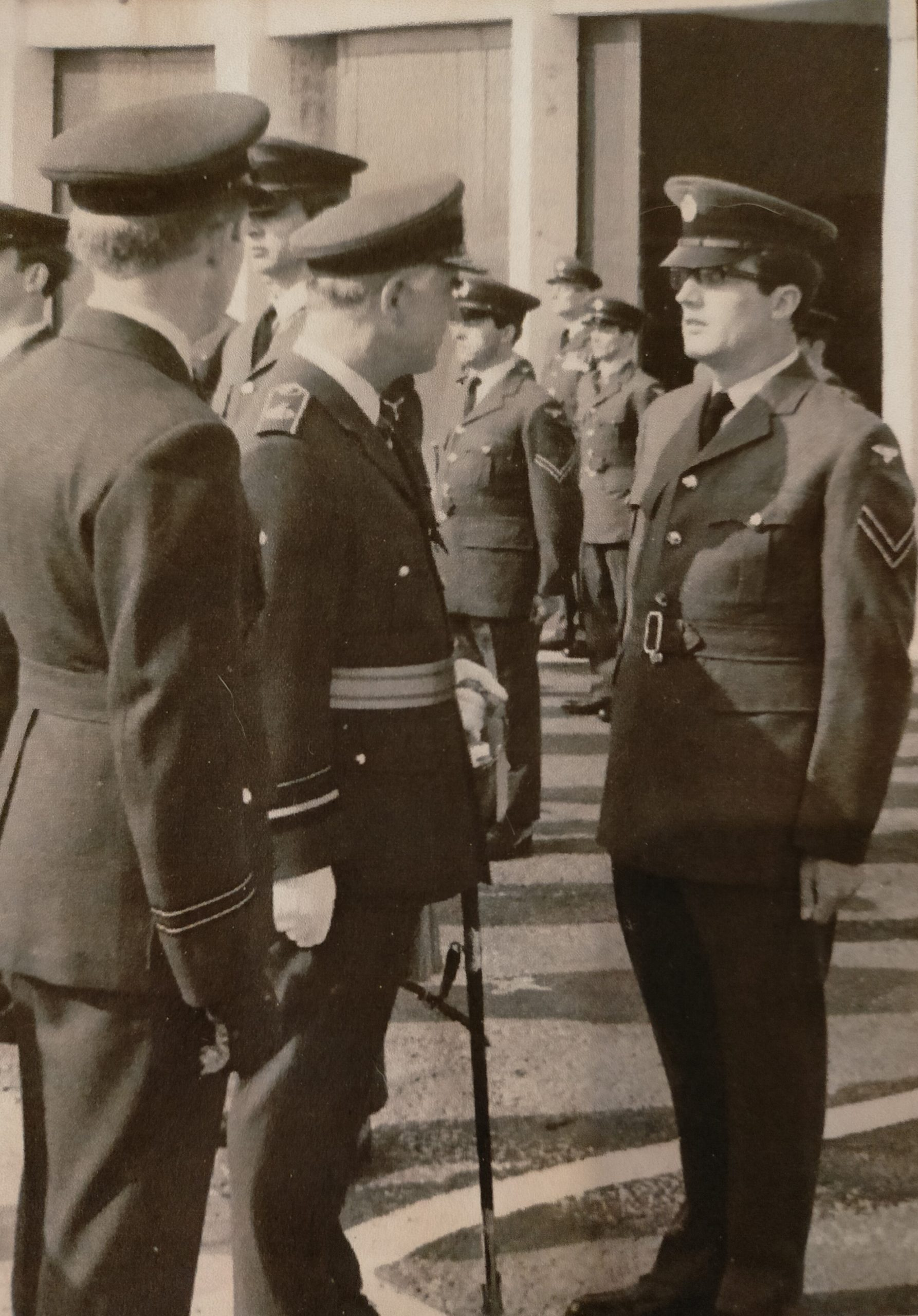 Corporal John Evans and several other men standing in uniform during an inspection.